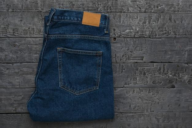Jeans bleus pour hommes sur une table en bois sombre. vêtements en denim classiques. mise à plat. la vue du haut.