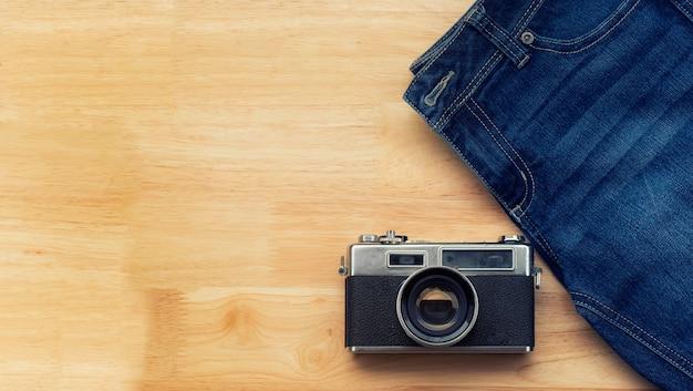 Jeans et caméras rétro lay sur le plancher en bois