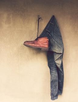Jeans et chaussures en cuir accrochés au mur