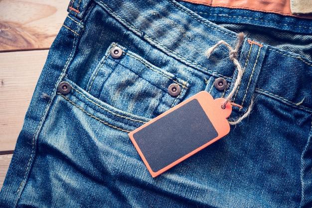 Jeans avec une étiquette de prix fixée sur le plancher de bois