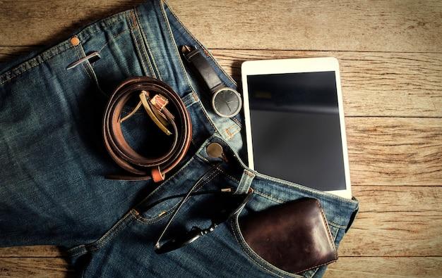 Jeans portefeuille et ceinture montres lunettes sur fond de bois, vue de dessus