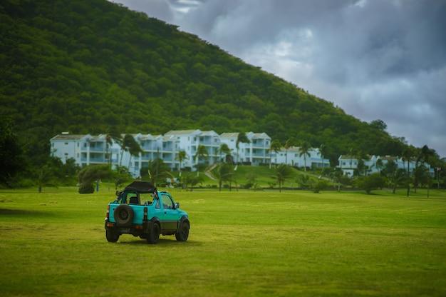 Jeep verte sur terrain d'herbe verte avec des maisons de montagne et blanches en arrière-plan avec un ciel bleu.