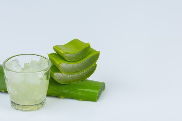 Jel d'aloe vera dans un verre avec des feuilles d'aloe vera est presque ensemble sur un mur blanc.