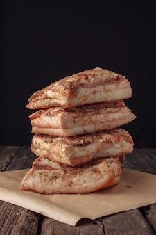 Jerky lard quatre pièces. la texture fibreuse du bacon et des épices est clairement visible. les produits de viande et le saindoux sont sur le comptoir.