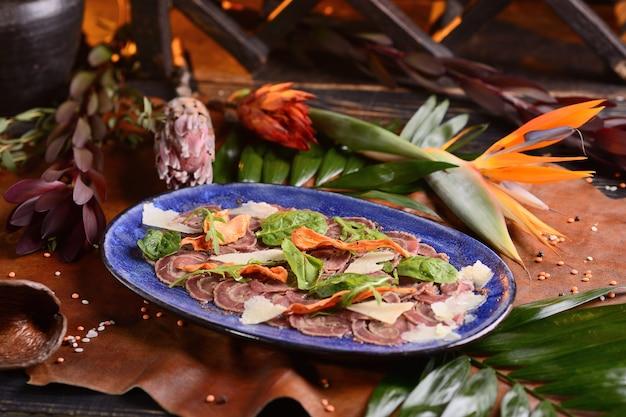 Jerky et parmesan en tranches. dans une assiette bleue. avec décor floral