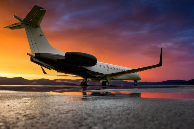 Jet d'affaires au coucher du soleil pittoresque après la pluie sur le tablier de l'aéroport