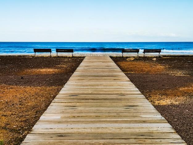 Jetée en bois et bleu océan et ciel en surface pour le concept de vacances de vacances d'été