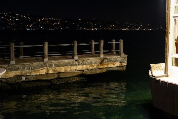 Jetée en bois avec corde dans la marina dans la nuit