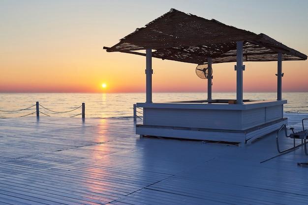 Jetée en bois sur un coucher de soleil orange fantaisie.