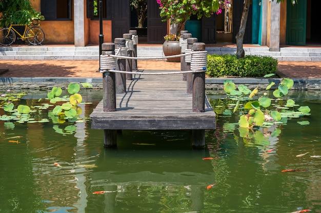 Jetée en bois sur étang dans un jardin tropical à danang, vietnam. concept de voyage et de nature