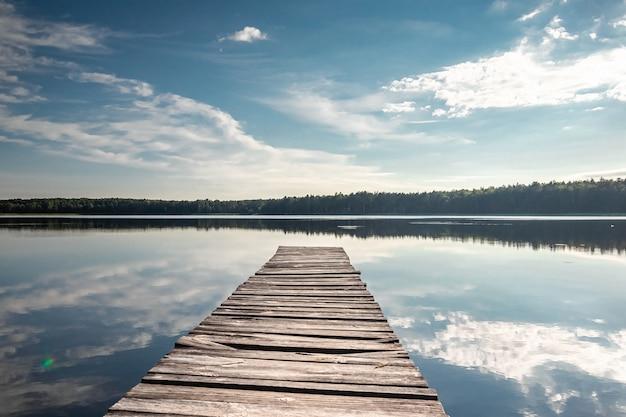 Jetée en bois sur le magnifique paysage de l'aube d'été du lac. copiez l'espace.