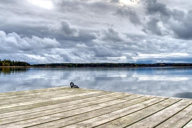 Jetée en bois pour petits bateaux, vue sur l'étang et beau ciel