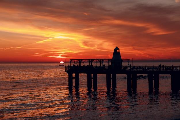 Jetée du phare et coucher de soleil sur l'eau
