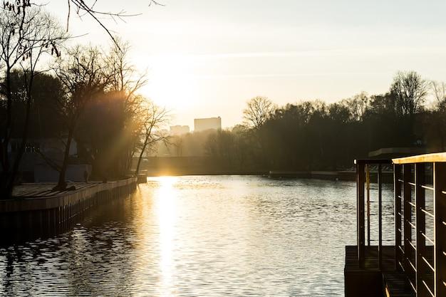 Jetée sur le lac dans le parc de la ville coucher de soleil d'automne un beau chemin du soleil sur l'eau