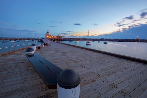 Jetée de st. kilda au crépuscule avec des bateaux dans le port