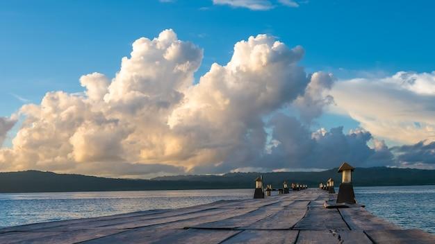 Jetée de la station de plongée sur l'île de kri. clound au-dessus de l'île de gam en arrière-plan. raja ampat, indonésie, papouasie occidentale.
