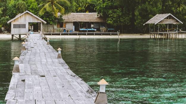 Jetée de la station de plongée sur l'île de kri. clound au-dessus de l'île de gam. raja ampat, indonésie, papouasie occidentale.