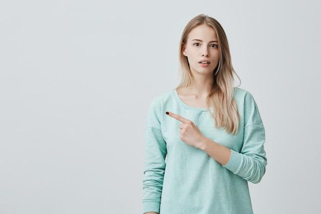 Jetez un coup d'œil à la jeune femme excitée séduisante et excitante en pull bleu, pointant les doigts de côté après avoir regardé avec surprise, avec une expression de visage joyeuse et excitée.
