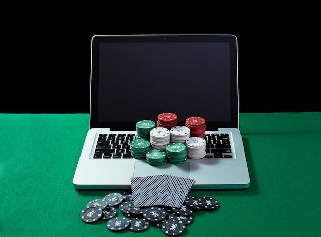 Jetons et cartes de casino sur le bloc-notes du clavier à la table verte