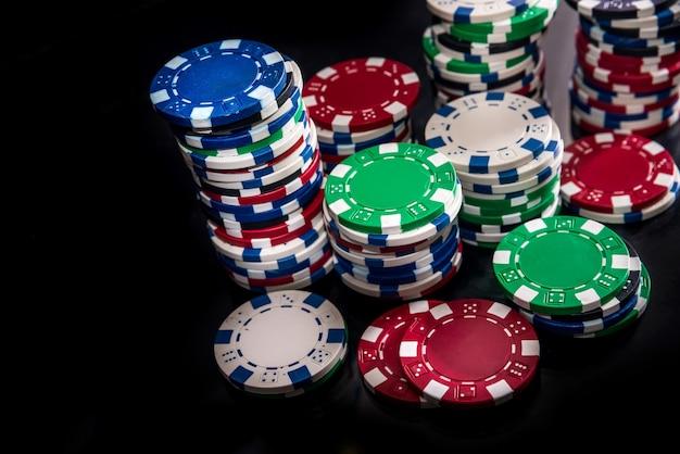 Jetons de casino colorés sur fond sombre libre