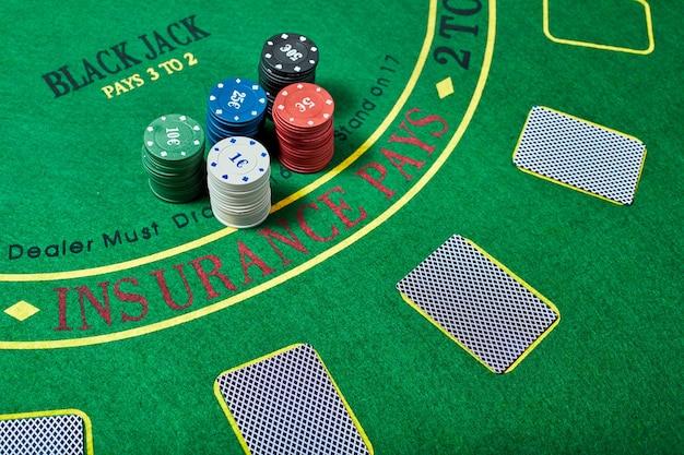 Jetons de casino et jeu de cartes allongé sur une table de casino verte, concept de jeu de poker, vue de dessus.