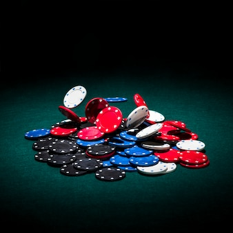 Jetons de casino multicolores sur table de poker verte