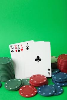 Jetons de jeu et carte de poker sur mur vert. vue de dessus
