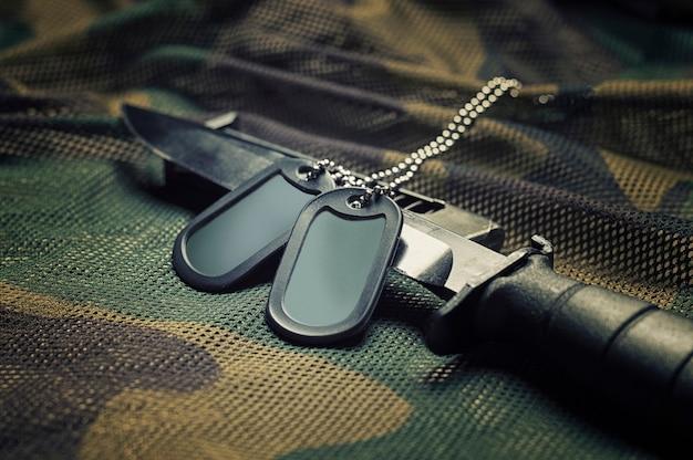 Les jetons militaires sont sur le couteau. le concept de l'armée, de la guerre, du conflit politique.