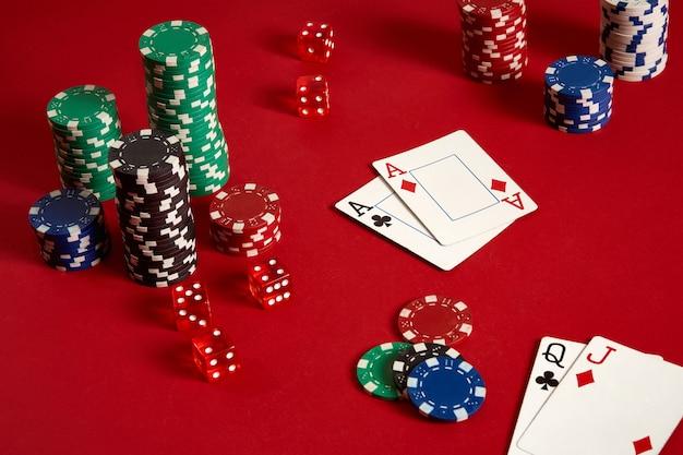 Jetons de poker et as sur fond rouge. groupe de jetons de poker différents. fond de casino. espace de copie. nature morte. une paire