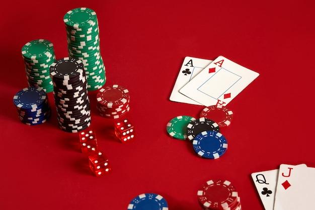 Jetons de poker et as sur fond rouge. groupe de jetons de poker différents. fond de casino.