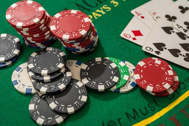 Jetons de poker avec des cartes à jouer sur la table de casino verte