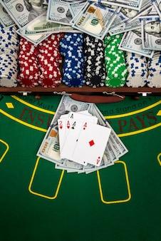 Jetons de poker dans le cas sur une table de jeu avec des cartes et des dollars.