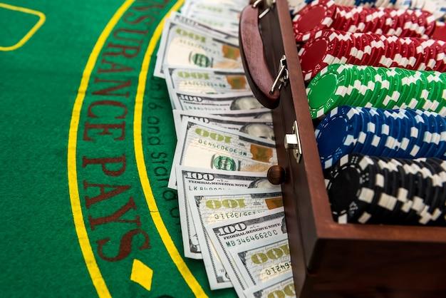 Jetons de poker et dollars dans un cas sur la table de jeu.