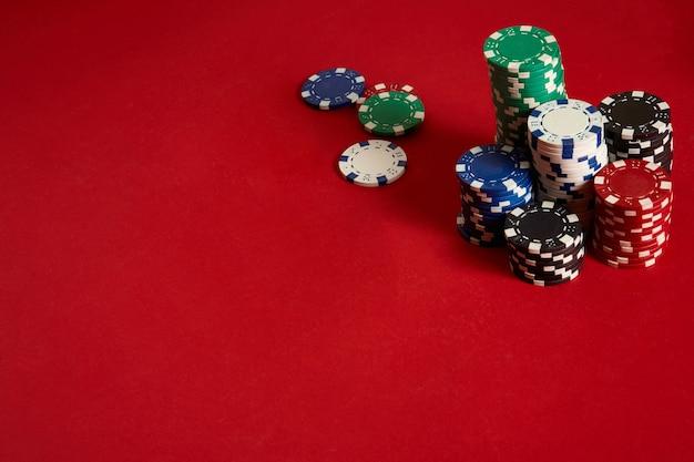 Jetons de poker sur fond rouge. groupe de jetons de poker différents. fond de casino.