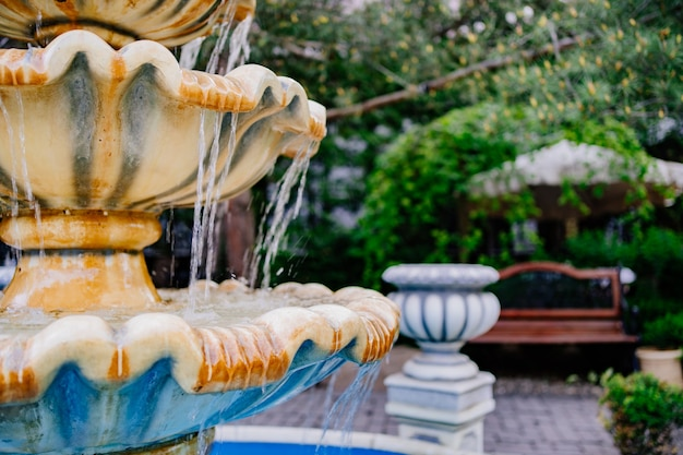 Des jets d'eau s'écoulent dans la fontaine. partie de la fontaine. aménagement paysager et décoration du parc ou du jardin. vacances d'été dans la nature.