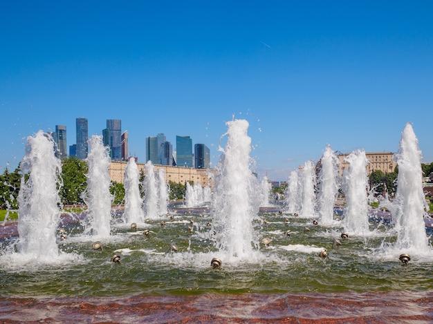 Jets de fontaines sur fond de gratte-ciel et ciel bleu sans nuages