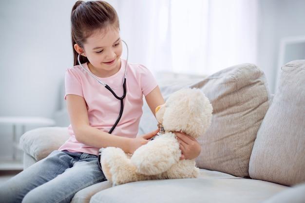 Jeu amusant. belle fille ambitieuse intelligente écoute ours en peluche assis sur un canapé et regardant vers le bas