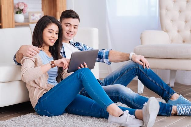 Jeu amusant. charmant couple gay posant sur le sol tout en regardant l'écran de la tablette