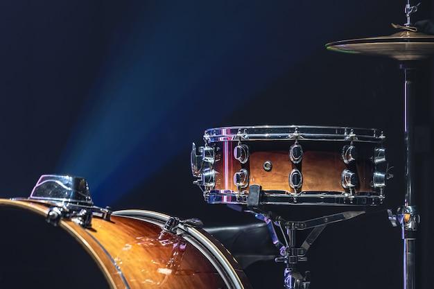 Jeu de batterie dans une pièce sombre avec un bel éclairage, caisse claire, cymbales, grosse caisse.