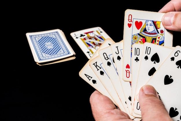 Jeu de cartes de poker sur une table. main tenant des cartes montrant son jeu