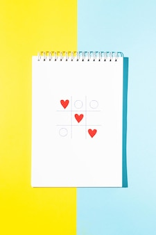 Jeu de cartes de voeux de la saint-valentin de tic-tac-toe vaincu les coeurs sur fond bleu et jaune