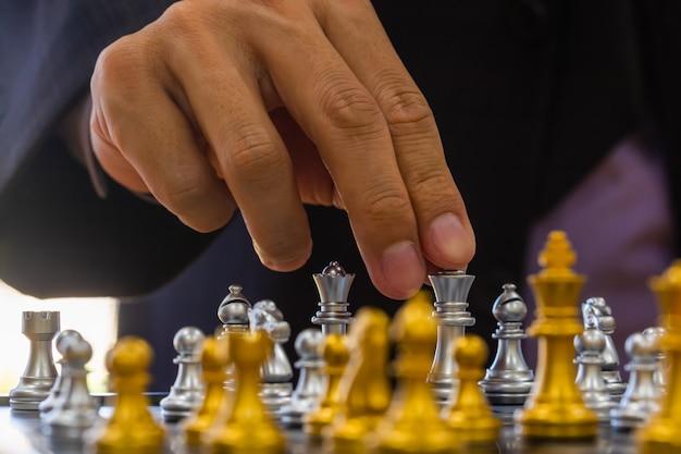 Jeu d'échecs sur l'échiquier derrière le fond de l'homme d'affaires.