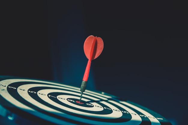 Le jeu de fléchettes a une flèche de fléchette rouge frappant le centre d'une cible de tir