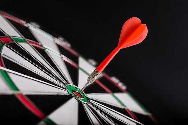 Jeu de fléchettes avec flèche rouge au centre du jeu de fléchettes.