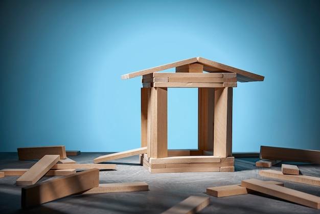 Jeu jenga, une maison en blocs de bois sur fond bleu