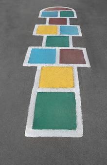 Jeu de marelle dessiné avec une peinture colorée sur le sol asphalté, vu d'en haut.