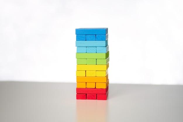 Jeu de plateau. tour de cubes en bois multicolores sur fond blanc.