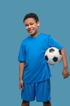 Jeu préféré. écolier de sport afro-américain debout avec un ballon de football à l'air affable en photo de studio