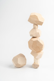 Jeu de puzzle tumi-ishi. un élément à côté d'une tour en pierre en bois instable. un élément supplémentaire ou manquant.