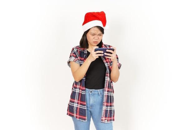 Jeu sur smartphone de la belle femme asiatique portant une chemise à carreaux rouge et un bonnet de noel